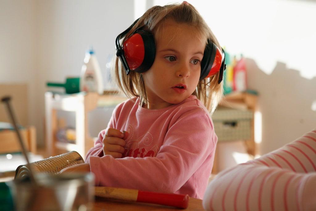 Kleines Mädchen mit Werkzeug und Gehörschutz