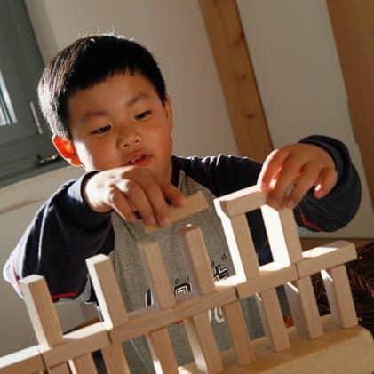 Junge mit Bauklötzen im Kindergarten quadrat