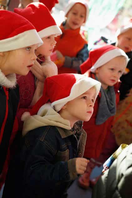 Kinder mit Nikolausmützen feiern Weihnachten