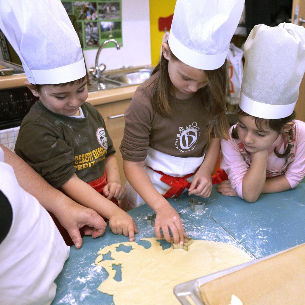 Kinder im Kindergarten stechen Plätzchen mit Form aus