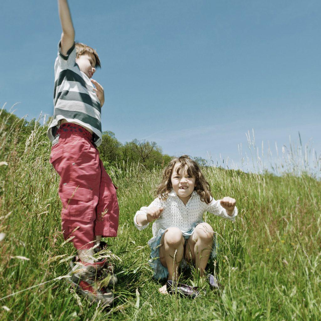 Junge und Mädchen spielen auf Wiese