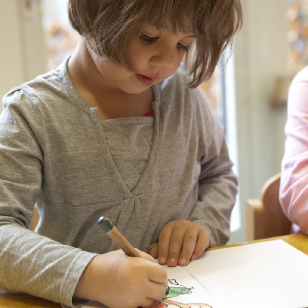 Mädchen malt im Kindergarten mit Buntstiften auf Papier