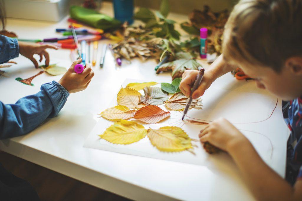 Kinder malen Herbstblätter im Kindergarten