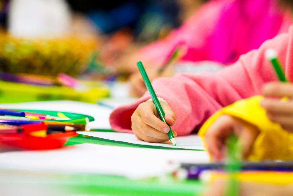 Kind malt mit einem Buntstift