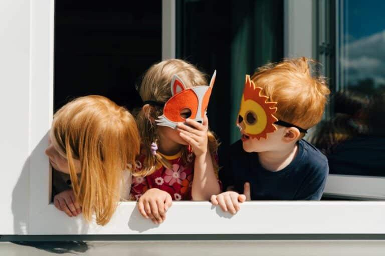 3 Kinder mit Tiermasken stehen lachend am Fenster