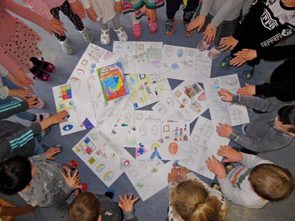 Kindergartenkinder stehen um gemalte Adapteo-Malbilder einer Sampling-Aktion